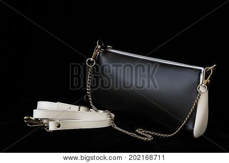 Close-up of leather handbag, always classic combination, black and white color with strap and chain, low key. For modern pattern, wallpaper or banner design