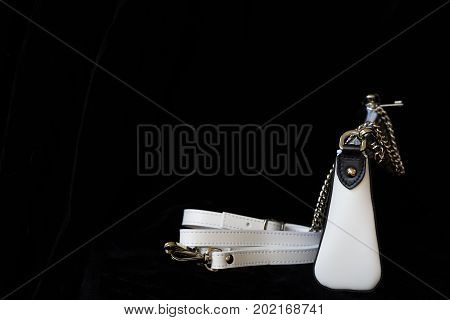 Close-up of leather handbag, always classic combination, black and white color with strap and chain, low key. Modern background or banner design,