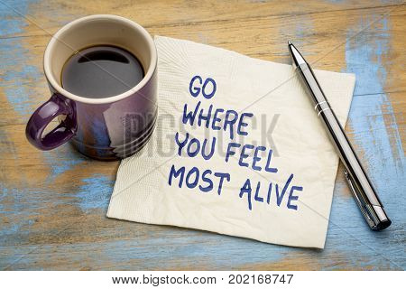 Go where you feel most alive - inspirational handwriting on a napkin with a cup of espresso coffee