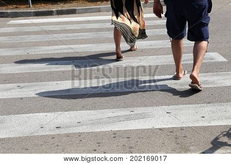 Close up of people walking on the zebra crossing to cross the road safely.