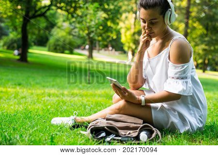 woman sitiing on the ground in the park and listening music