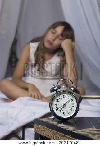 Early awakening. Alarm clock standing on bedside table. Wake up of an asleep young girl in bed on a background.