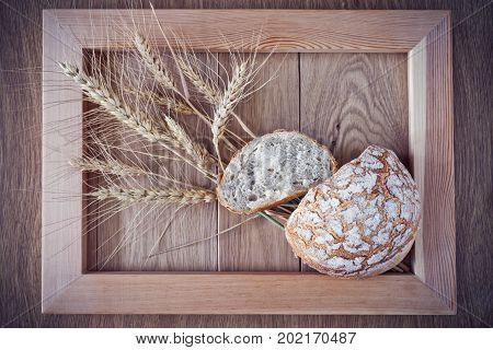 Round bread and spikelets of wheat in a wooden frame on a wooden surface