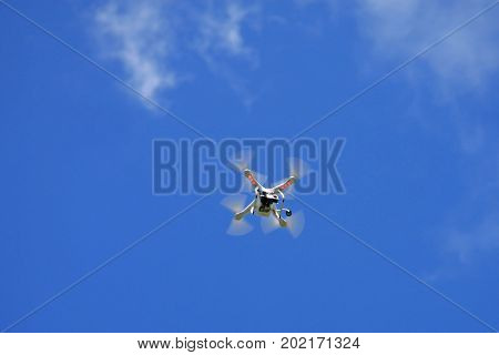 Remote control drone flying in a blue sky