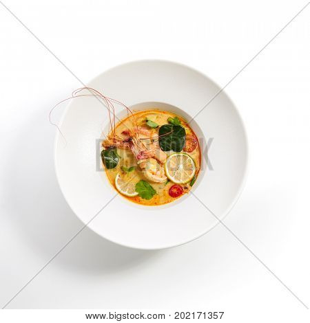 Tom yam kung - Thai soup with shrimp and coconut milk with slices of fruit and vegetables and fresh herbs in white plate. Pan-Asian menu in restaurant. Top View