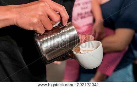 Barista Hand Pouring Fresh Milk Foam Into Espresso Cup