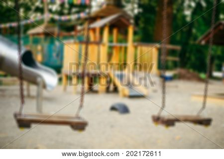 Empty chain swings on playground in the public park close up, blured concept