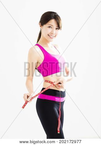 Fit young woman taking measurements of her body
