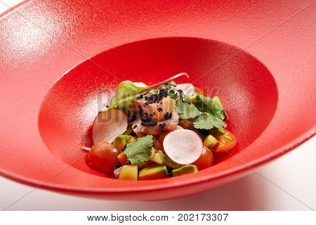 Menu in Pan-Asian cuisine - Tartar from tuna with passion fruit sauce with slices of vegetables and fresh greens on the red plate