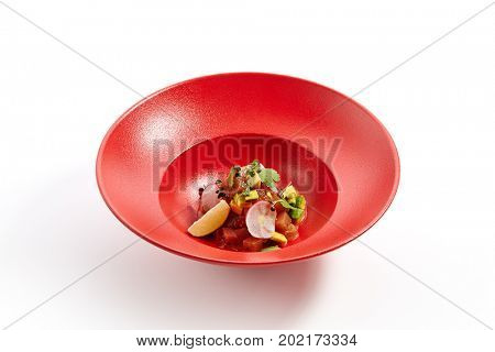 Menu in Pan-Asian cuisine - Tartar from salmon with passion fruit sauce with slices of vegetables and fresh greens on the red plate