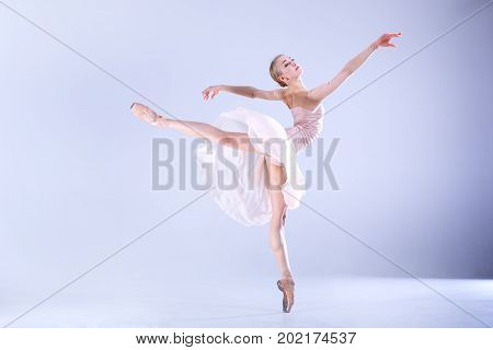 Young and slim ballerina in a dancing skirt is dancing in a white studio