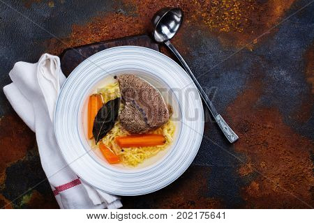 Broth soup in a plate with ladle on dark stone background. Top view. Copy space