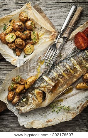 Baked sea bass with roasted potatoes on wooden table