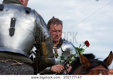 ST. PETERSBURG, RUSSIA - JULY 9, 2017: Armored knight on a horse holding a rose flower during the military history project Battle On Neva at St. Peter and Paul fortress. It's the 4th such event