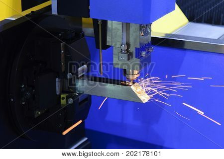 The CNC fiber laser cutting machine cutting the steel square pipe with the sparking light.The fire flame from the fiber laser cutting machine.
