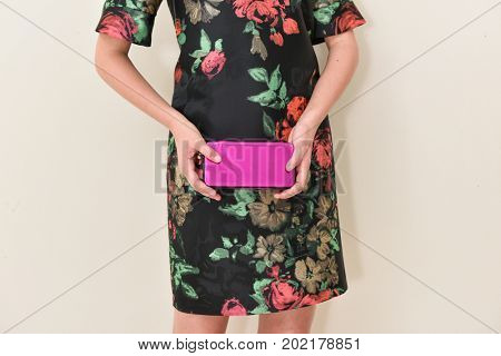 Beautiful female in floral sundress holding purse posing