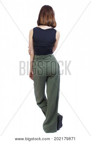 back view of standing young beautiful  woman.  girl  watching. Rear view people collection.  backside view of person. The top view of a girl in green stands in a relaxed pose