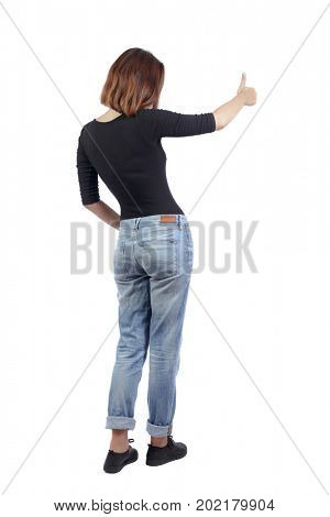 Back view of  woman thumbs up. Rear view people collection. backside view of person. Isolated over white background. A girl in jeans and a black T-shirt is sideways and is showing a thumbs-up