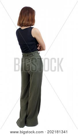 back view of standing young beautiful  woman.  girl  watching. Rear view people collection.  backside view of person. A girl in green trousers stands with her arms crossed
