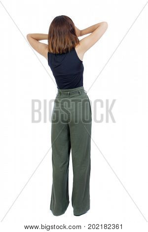 back view of standing young beautiful  woman.  girl  watching. Rear view people collection.  backside view of person. A girl in green trousers stands in horror clutching her hands behind her head
