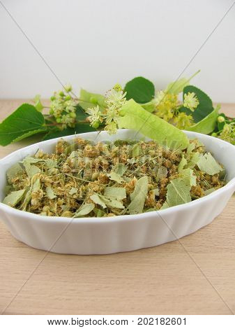 Fresh and dried linden flowers on a wooden board