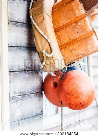 Safety equipment concept. Orange life jacket and buoy hanging outside on wooden wall.