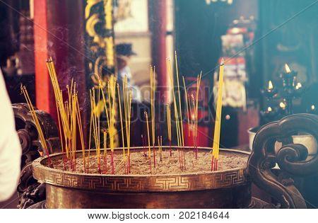 Burning incense sticks in a Buddhist Temple in Vietnam