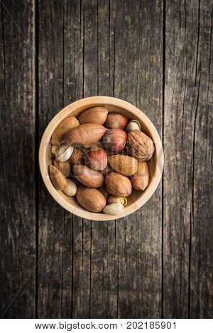 Different types of nuts in the nutshell. Hazelnuts, walnuts, almonds, pecan nuts and pistachio nuts in wooden bowl.
