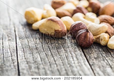 Different types of nuts. Hazelnuts, walnuts, almonds, brazil nuts and pistachio nuts on old wooden table.
