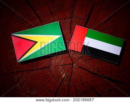 Guyana Flag With United Arab Emirates Flag On A Tree Stump Isolated