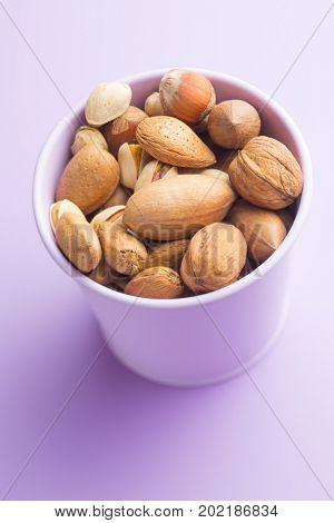 Different types of nuts in the nutshell in cup.