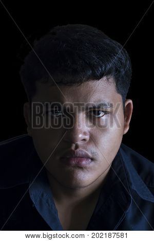 Portrait head shot of angry Asian Thai young man looking sharply towards camera on black background