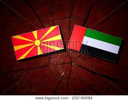 Macedonian Flag With United Arab Emirates Flag On A Tree Stump Isolated