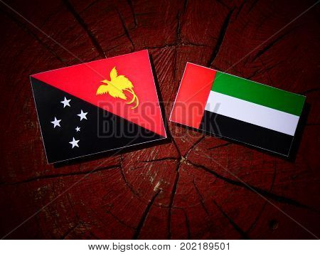 Papua New Guinea Flag With United Arab Emirates Flag On A Tree Stump Isolated