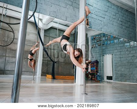 Young sexy slim woman pole dancing in grey interior.Beautiful, Attractive girl performing pole dance. Shot with industrial concrete background.Lady with good figure dancing on pylon