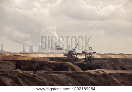 Germany North Rhine Westphalia -june 2017: ground excavator in action moving mullock and soil at open pit coal mine; Germanyfor winning brown coal