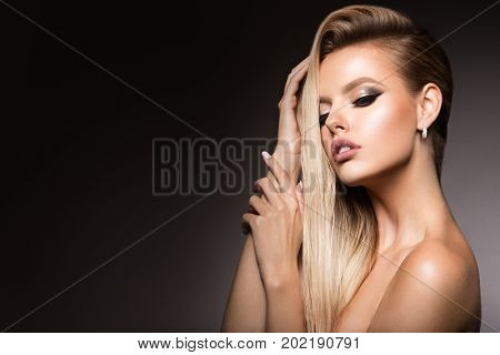 Glamour portrait of beautiful girl model with makeup and romantic hairstyle. Fashion shiny highlighter on skin, sexy gloss lips make-up and dark eyebrows.