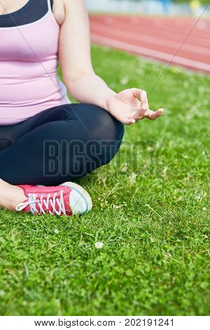 Over-sized female in activewear sitting on green lawn with her legs crossed