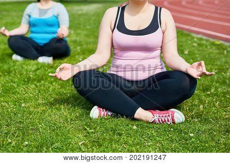 Cross-legged plump females practicing yoga exercises outdoors