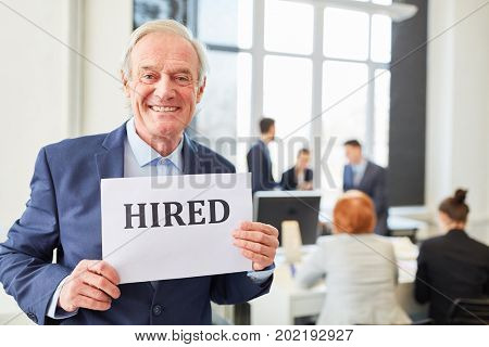 Senior has succes at looking for job and holds sign with