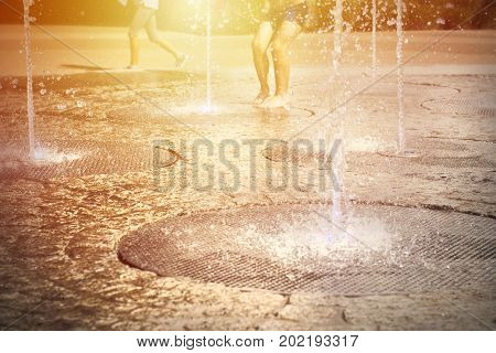 People enjoy sun and summer and water fountains form the ground