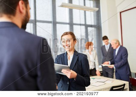 Business woman welcomes business partner to negotiation meeting