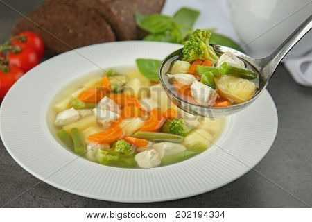 Ladle and plate with delicious turkey soup on table