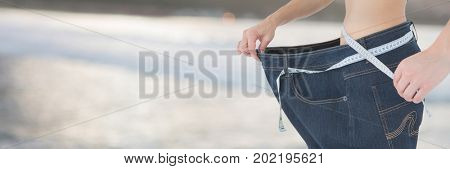 Digital composite of Slim healthy woman holding measuring tape  and large trousers fitting