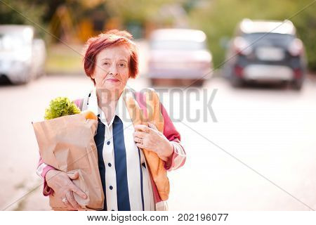 Happy senior woman 70-80 year old holding package of food walking on street outdoors. Looking at camera. Healthy eating.