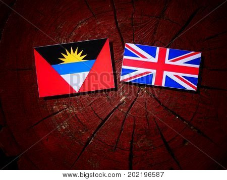Antigua And Barbuda Flag With British Flag On A Tree Stump Isolated