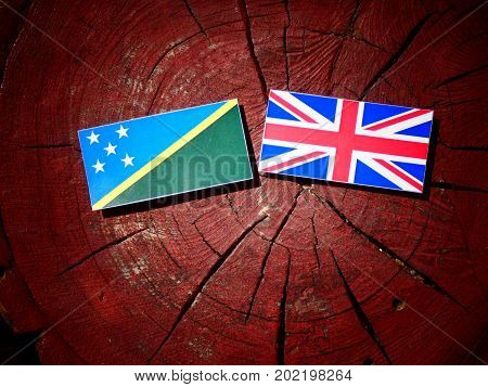 Solomon Islands Flag With British Flag On A Tree Stump Isolated