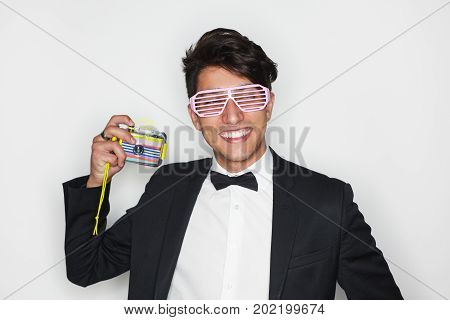Smiling brunette man in flip glasses wearing black suit with bow tie holding still camera.