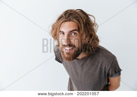 Photo of caucasian handsome young bearded happy man standing isolated over grey wall. Looking camera.