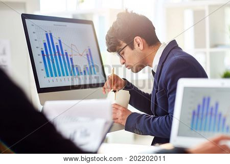 Busy handsome manager in suit eating instant noodles with chopsticks while sitting at desk in open plan office, profile view